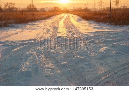 A snowy road in the suburbs during sunset