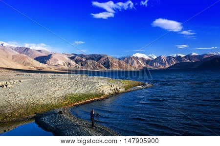 LADAKH, INDIA - JUNE 16, 2012: An photographer walking on Pangong Lake in Ladakh, Jammu and Kashmir State, India