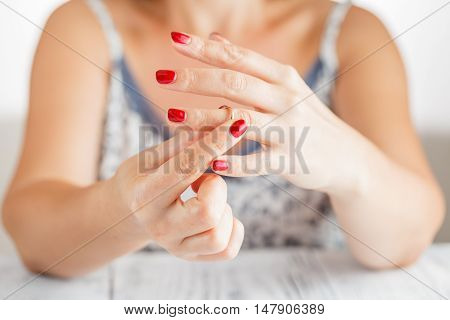 Woman taking off the wedding ring from finger