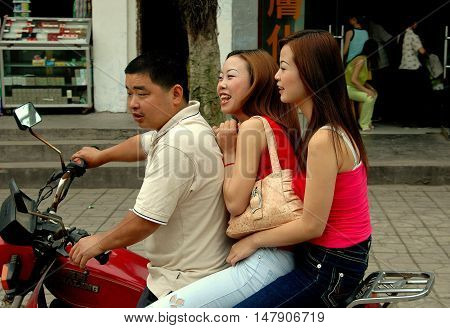 Huang Long Xi China - April 27 2005: Man with two stylish women riding a motorcycle past a row of shops