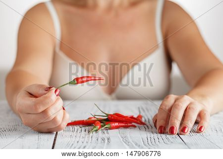 Sexy woman with red chili pepper in hand