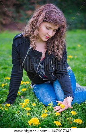 Young woman looking down sitting in a field of yellow dandelion flowers in grass smiling and holding them