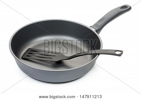 Black Frying Pan With Cooking Utensils: Plastic Paddle, Isolated On White Background, Close-up.