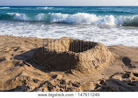 Simple castle in the sand, made by kids on a beach of Kos island, Greece