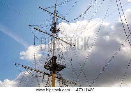 Ship's mast sailboat on a background of clouds in the sky. The romance of travel and far wandering. Background marine themes. Ocean transport ship under sail.
