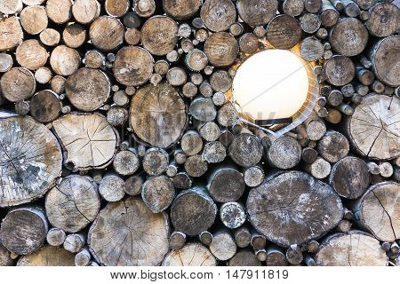 Closeup of woodpile with a glowing lamp