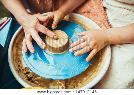 a child working on the potter's wheel makes the shape of a new product
