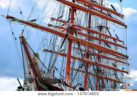 Masts of wooden sailing ship, detailed rigging against blue sky and clouds