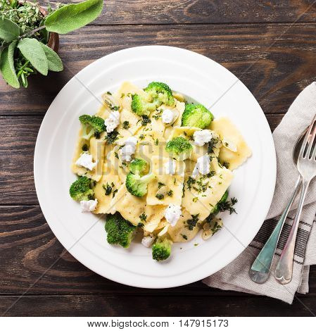 Italian ravioli with goat cheese, broccoli and herbs on old wooden background. Healthy food. Top view.