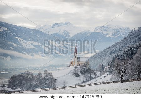 St. Pankraz church in an alpine landscape in the snow surrounded by clouds and fog on a hill with a sublime view over Zillertal valley with the Alps mountains in the background in Fuegen Austria in winter.
