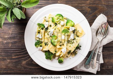 Italian ravioli with goat cheese, broccoli and herbs on old wooden background. Healthy food. Top view. Copy space.