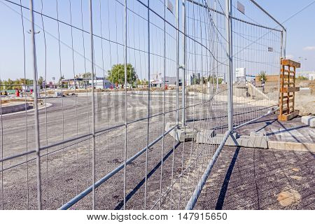 Mobile steel fence as a barrier. Restricted area for the authorized personnel only. Construction site has a safety rules.