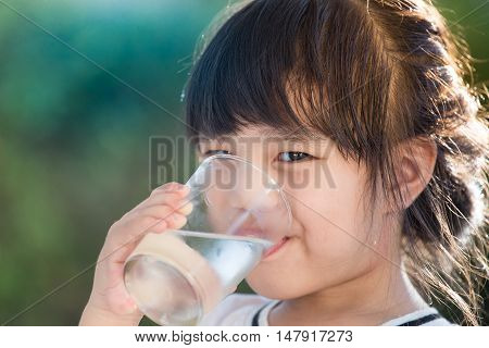 Closeup of little asia girl drinking water