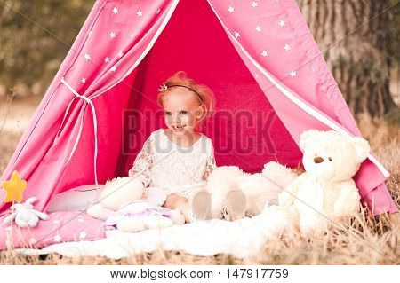 Smiling baby girl 3-4 year old playing outdoors with pink wigwam toys. Childhood.