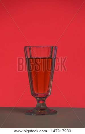 Crystal glass with a drink on a red background