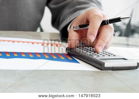 Closeup of Male Hand with Pen Using Calculator