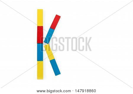 Capital letter K made up of different color wooden rectangular blocks isolated on a white background