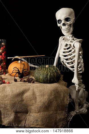 Halloween skeleton holding a brush and painting pumpkins and decorations for the celebration
