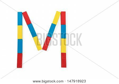 Capital letter M made up of different color wooden rectangular blocks isolated on a white background