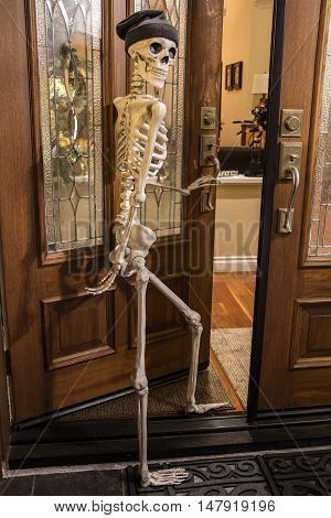 Halloween skeleton greeting at the door wearing a knitted hat