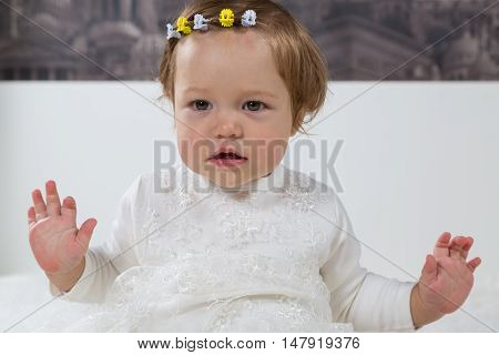 Little girl is sitting with hands raised