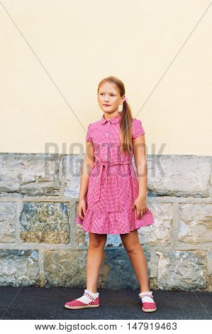 Outdoor portrait of cute little 8 year old girl, wearing red mary jane dress