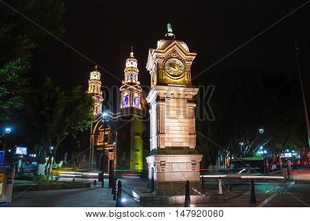 Major central park and square in Puebla de Zaragoza, Mexico with illuminated clock tower and Cathedral