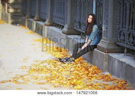 Portrait of a sad long-haired girl sitting on a stone curb around the metal fence in autumn sunny day.