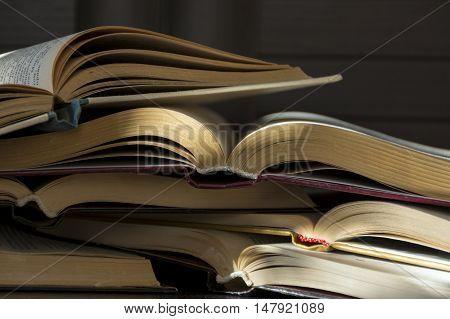 several open books lying on dark background