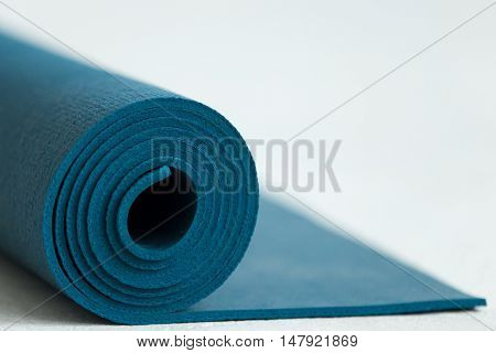 Rolled up blue yoga pilates or fitness mat on the floor copy space close up