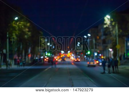 View of the street in the city at night blurred where riding cars trams people walking glow lights and vehicle headlights.