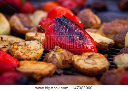 Red bell pepper and potatoes grilled until golden brown. The concept of proper nutrition and a healthy lifestyle. Cooking vegetables on the barbecue.