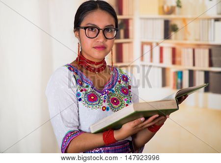 Beautiful young lawyer wearing traditional andean blouse and glasses, holding book reading, bookshelves background.