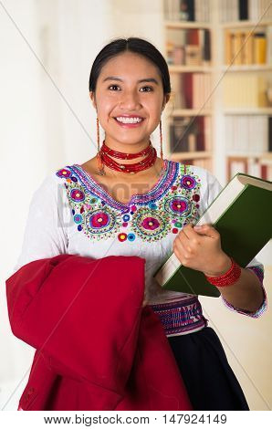Beautiful young lawyer wearing traditional andean blouse, holding red jacket and green book smiling to camera, bookshelves background.