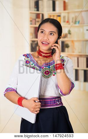 Beautiful young lawyer wearing traditional andean blouse and red necklace, holding laptop talking on phone smiling, bookshelves background.