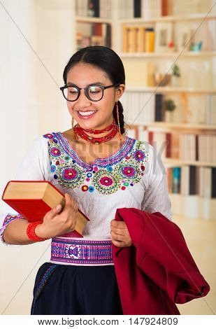 Beautiful young lawyer wearing traditional andean blouse, glasses and necklace, holding red jacket with one hand, thick book in other, smiling happily, bookshelves background.