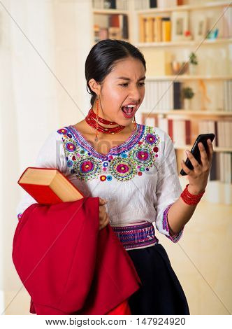 Beautiful young lawyer wearing traditional andean blouse with necklace, holding red jacket and book while using mobile phone, looking shocked at screen, bookshelves background.