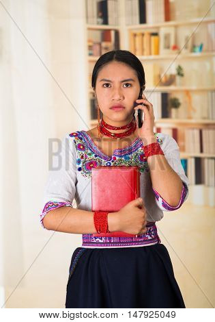 Beautiful young lawyer wearing black skirt, traditional andean blouse with necklace, standing posing for camera, holding red book and talking on phone, serious facial expression, bookshelves background.