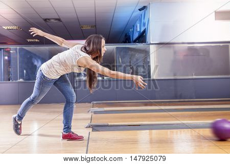 young girl pulls the ball on the bowling alley