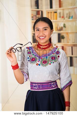 Beautiful young lawyer wearing black skirt, traditional andean blouse with necklace, standing posing for camera, holdig glasses, smiling happily, bookshelves background.