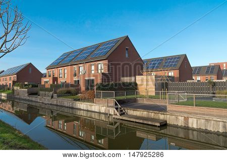 modern terraced houses with solar panels in a newly build residential area in the netherlands