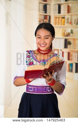 Beautiful young lawyer wearing black skirt, traditional andean blouse with necklace, standing posing for camera, holding red book reading happily, bookshelves background..