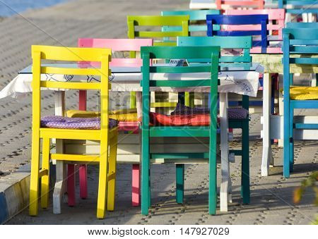 Colorful wooden chairs.  Characteristic restaurant with table and colorful chairs on the beach.