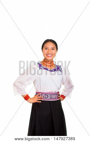 Beautiful young woman standing wearing traditional andean blouse and red necklace, holding arms on hips while smiling happily, white studio background.