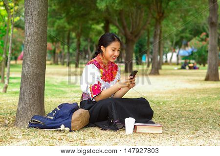Young woman wearing traditional andean skirt and blouse with matching red necklace, sitting on grass next to tree in park area, texting using mobile phone while smiling happily.