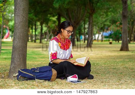 Young woman wearing traditional andean skirt and blouse with matching red necklace, sitting on grass next to tree in park area, relaxing while reading book, smiling happily.