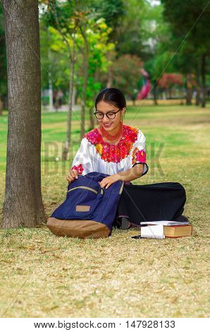 Young woman wearing traditional andean skirt and blouse with matching red necklace, sitting on grass next to tree in park area, relaxing while looking into backpack, smiling happily.