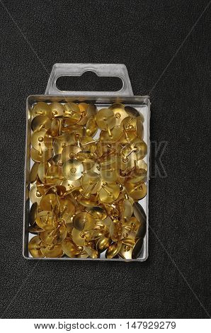 Thumb tacks in a container isolated on a black background