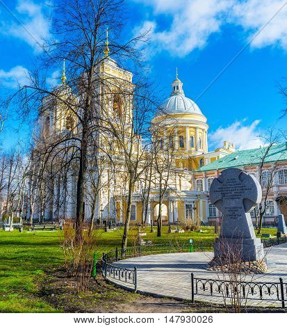 SAINT PETERSBURG RUSSIA - APRIL 25 2015: The memorial cross in garden of Alexander Nevsky Lavra and the Holy Trinity Cathedral behind the trees on April 25 in Saint Petersburg.
