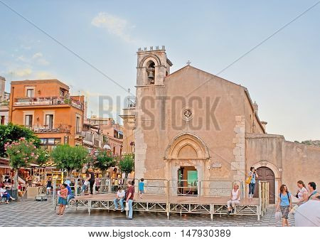TAORMINA ITALY - OCTOBER 1 2012: The medieval St Augustine Church serving as a library located in the crowded IX Aprile (Ninth of April) Square surrounded by outdoor cafes and blooming trees on October 1 in Taormina.